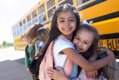 Standing at the head of the bus line, the two elementary age best friends give each other a hug.